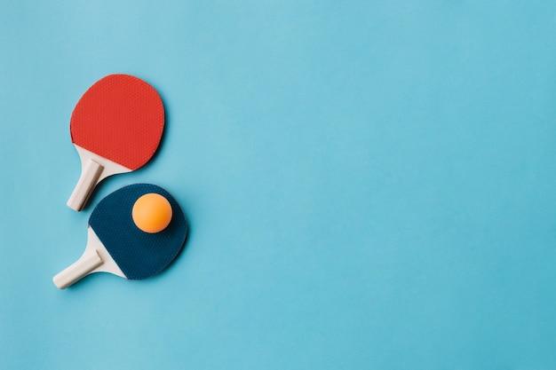Schöne tischtennisschläger mit ball über blauen untergrund