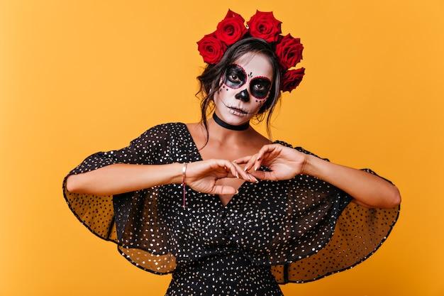 Schöne tote frau, die in halloween auf gelber wand aufwirft. wunderbarer weiblicher zombie im rosenkranz.