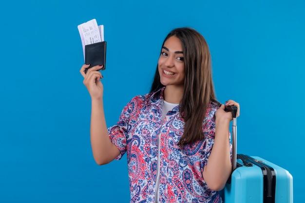 Schöne touristenfrau, die reisekoffer und reisepass mit eintrittskarten mit lächeln auf gesicht glücklich und positives reisekonzept hält, das über blauem raum steht