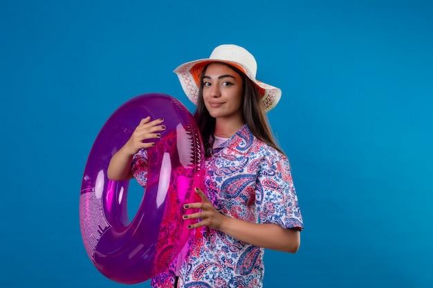 Schöne touristenfrau im sommerhut, der mit aufblasbarem ring bereit steht, über vereinzeltem blauem raum urlaub zu machen