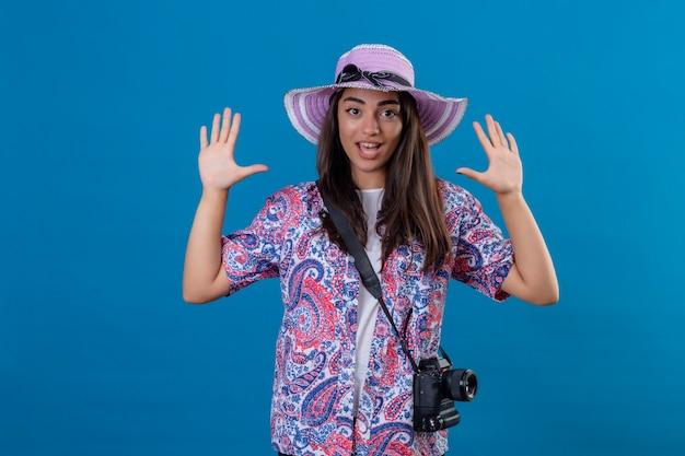 Schöne touristenfrau im sommerhut mit der fotokamera, die hände in der übergabe anhebt, die überrascht steht, über isoliertem blauem raum zu stehen