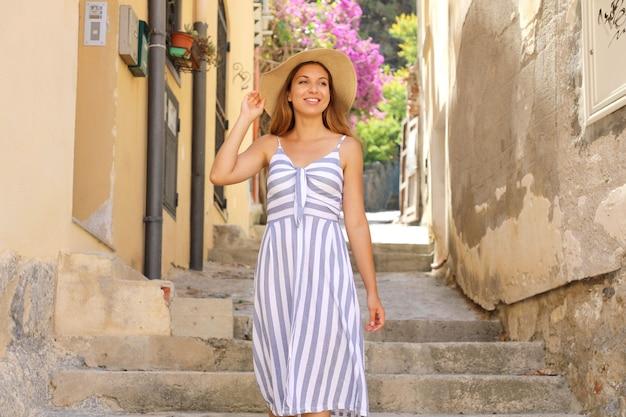 Schöne touristenfrau mit hut und kleid, die in der gemütlichen italienischen straße in cefalu, sizilien, italien gehen