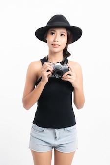 Schöne touristin, die einen schwarzen hut und eine jeansjacke trägt, steht, um ein foto mit einer vintage-kamera zu machen.