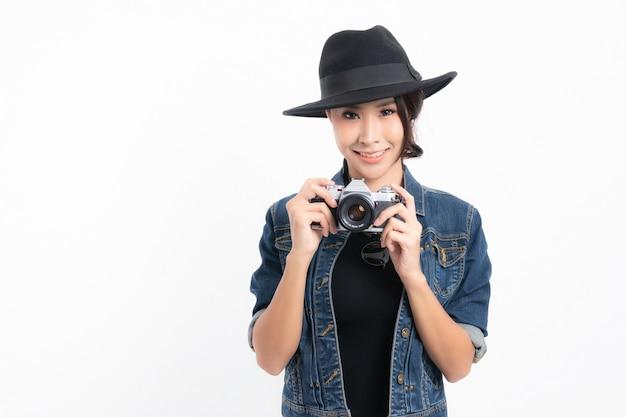 Schöne touristin, die einen schwarzen hut und eine jeansjacke trägt, steht, um ein foto mit einer vintage-kamera zu machen