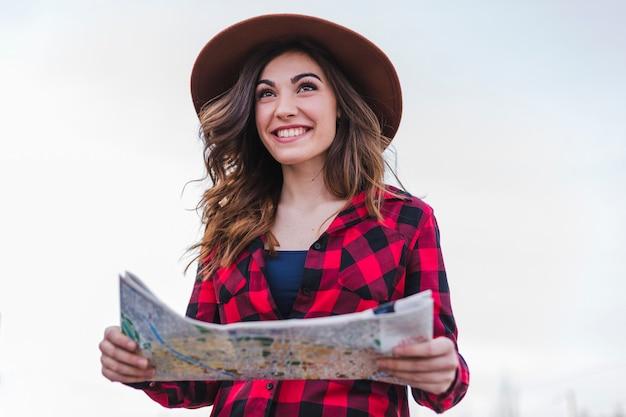 Schöne touristische frau, die eine karte schaut