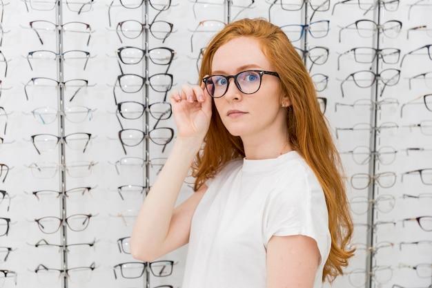 Schöne tragende brillen der jungen frau, die kamera im optikershop betrachten