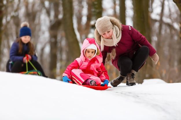 Schöne tragende jacke und strickmütze des kleinen mädchens, die in einem park des verschneiten winters spielen