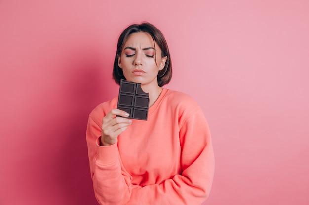Schöne traurige frau mit bauchschmerzen mit schokoriegel auf rosa hintergrund und hellem make-up