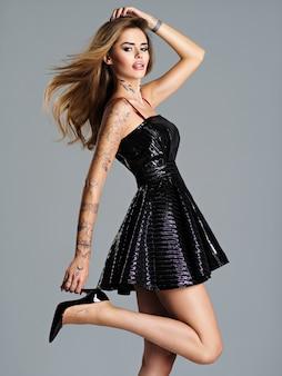 Schöne trendige frau im schwarzen kleid mit einem tattoo auf der hand. modeporträt des jungen weiblichen modellmädchens mit den langen haaren, die im studio aufwerfen.
