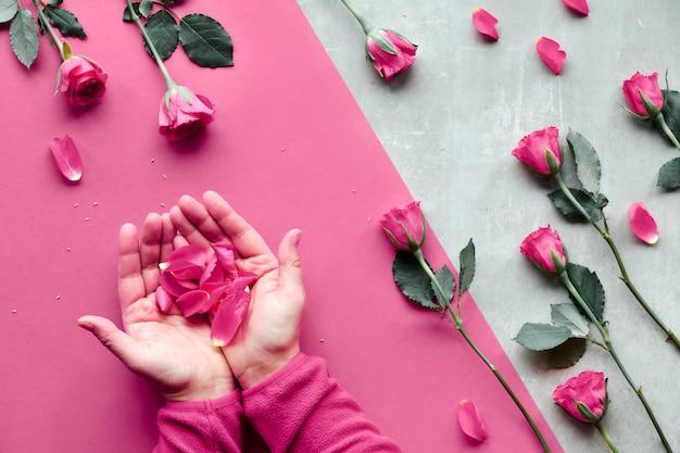 Schöne trendige geometrische wohnung lag in roten und natürlichen farben mit korallenroten rosen. weibliche hände in flauschigem rotem vlies in form eines herzens. valentinstag, muttertag oder geburtstagsarrangement.