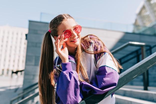 Schöne trendige junge frau in stilvollen kleidern, die mit lächeln aufwerfen