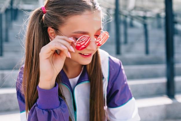 Schöne trendige junge frau in stilvollen kleidern, die rosa sonnenbrille tragen und lächeln