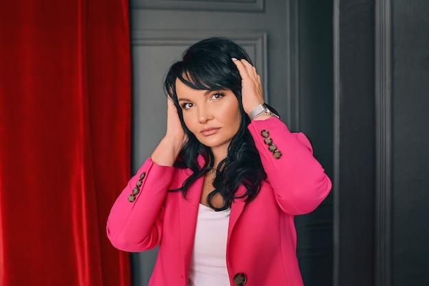 Schöne trendige schauspielerin frau entertainer in rosa anzug auf rotem samtvorhang hintergrund