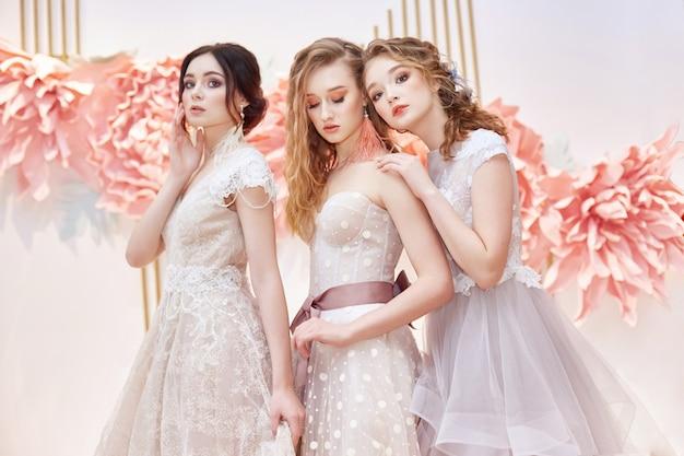 Schöne trio-bräute im teuren hochzeitskleid