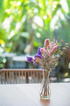 Schöne trockenblumen im glasvase auf hölzerner tabelle, restaurantinnenraum