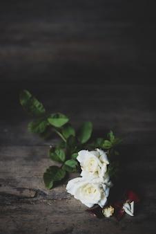 Schöne trockene rote und weiße rosen auf hölzernem hintergrund des schmutzes