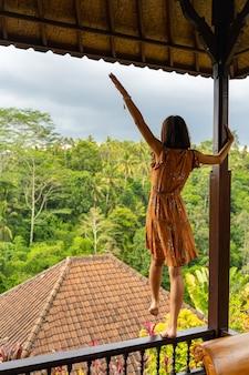Schöne tropische landschaft. hübsches brünettes mädchen, das auf der holzstütze steht und sich auf den regenwald freut
