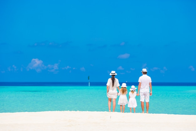 Schöne tropische strandlandschaft mit familie im weiß sommerferien genießend
