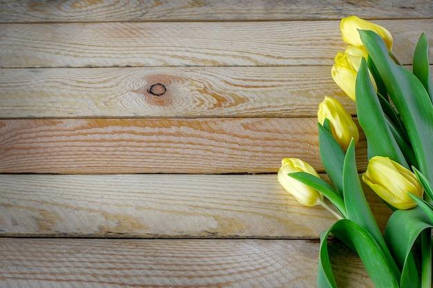 Schöne tulpen auf hölzernem hintergrund