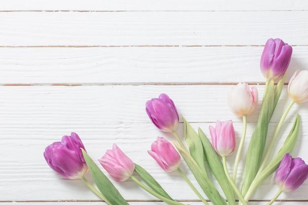 Schöne tulpen auf weißem hölzernem hintergrund