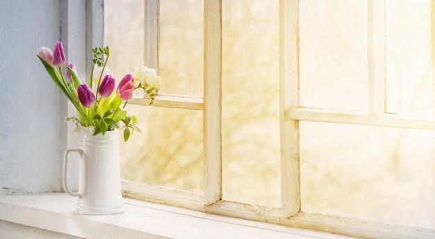 Schöne tulpen im krug auf altem weißem fensterbrett