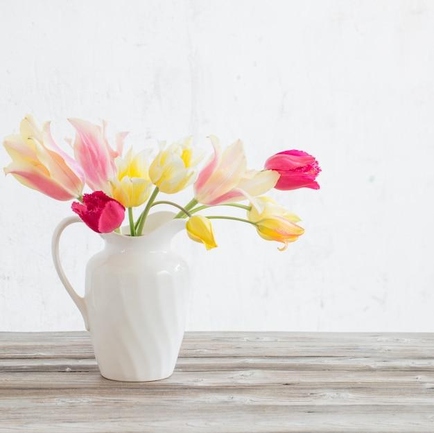 Schöne tulpen im weißen krug auf hölzernem hintergrund
