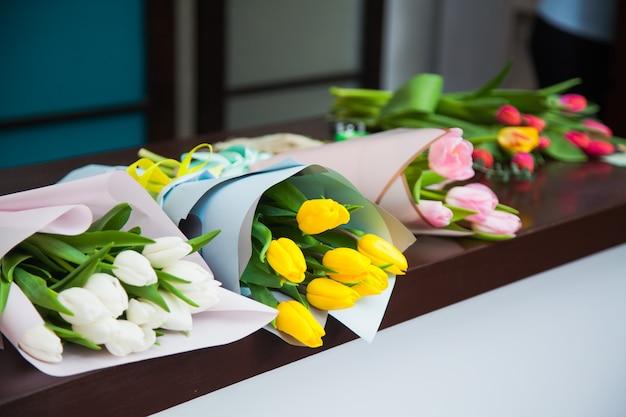 Schöne tulpen in bastelpapier liegen auf tisch bereit für die lieferung am 8. märz des frauentags. ein heller hintergrund der frühlingsblumenblüten. floristik und urlaubsvorbereitung. blumenmusterkonzept