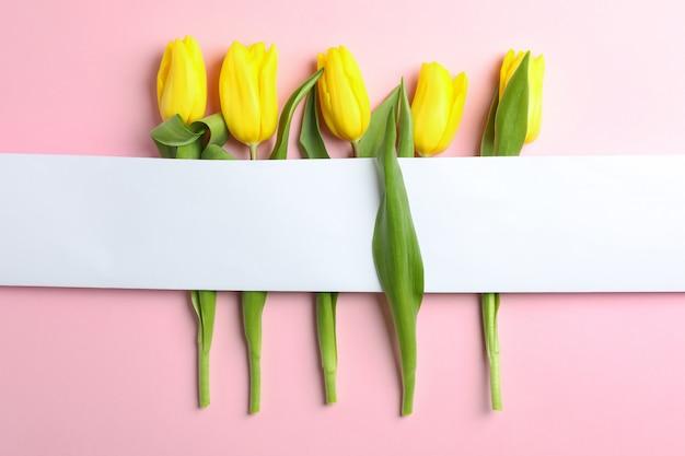 Schöne tulpen mit leerer karte auf licht, draufsicht. platz für text