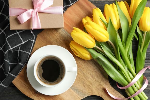 Schöne tulpen mit notizbüchern und tasse kaffee auf licht, draufsicht