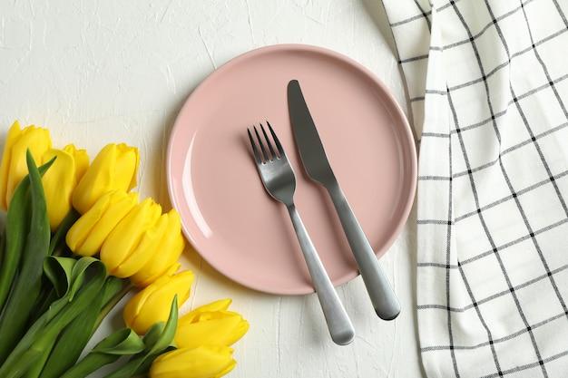 Schöne tulpen und teller mit utensilien für muttertag auf licht, draufsicht