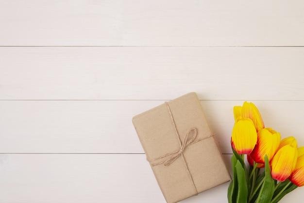 Schöne tulpenblume und geschenkbox auf hölzernem hintergrund mit romantischen geschenken für muttertag mit pastellton