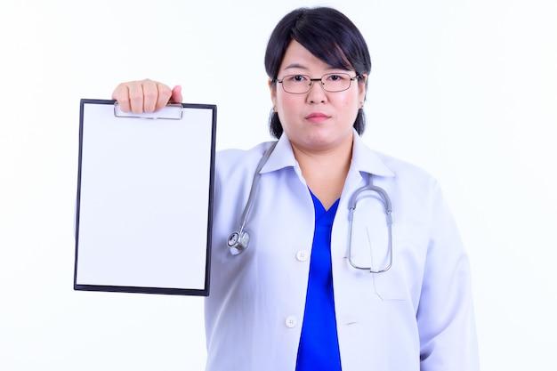Schöne übergewichtige asiatische ärztin mit kurzen haaren, die brillen tragen, isoliert gegen weiße wand