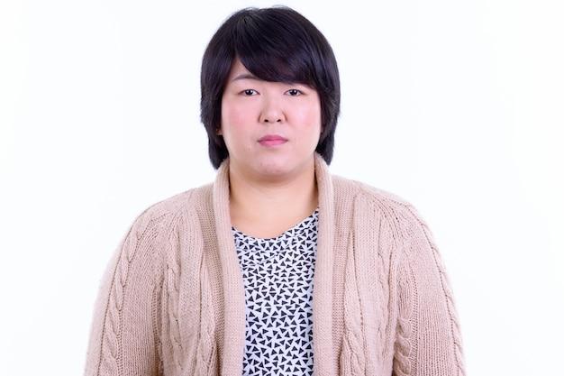 Schöne übergewichtige asiatische frau mit kurzen haaren bereit für den winter isoliert gegen weiße wand