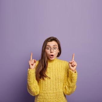 Schöne überraschte frau hat erschrockenen blick, zeigt auf etwas unglaubliches, trägt runde brille und gelben strickpullover, zeigt einige artikel im laden, isoliert über lila wand