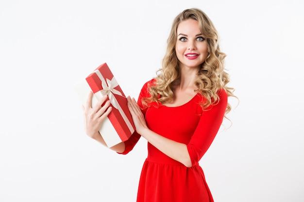 Schöne überraschte frau in einem roten kleid mit einer geschenkbox