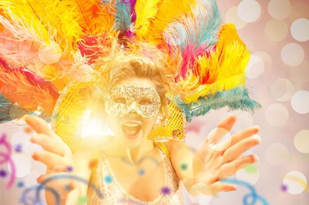 Schöne überraschte frau in karnevalsmaske schönheitsmodellfrau, die maskerademaske trägt