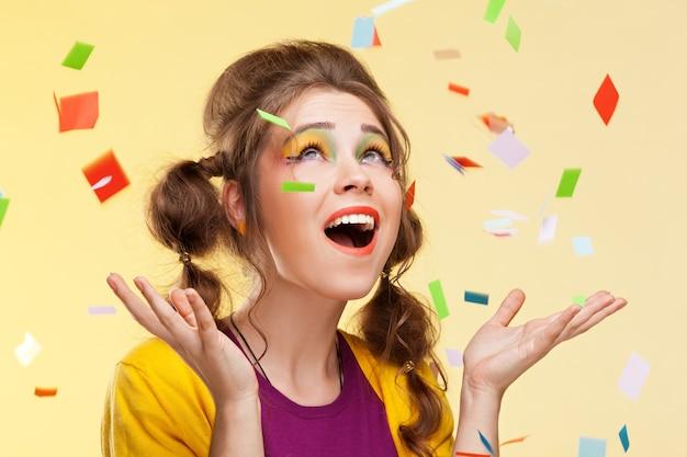 Schöne überraschte frau mit konfetti, die auf sie fallen
