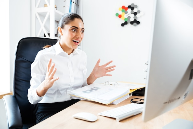 Schöne überraschte geschäftsfrau, die auf laptop schaut, während sie am schreibtisch sitzt