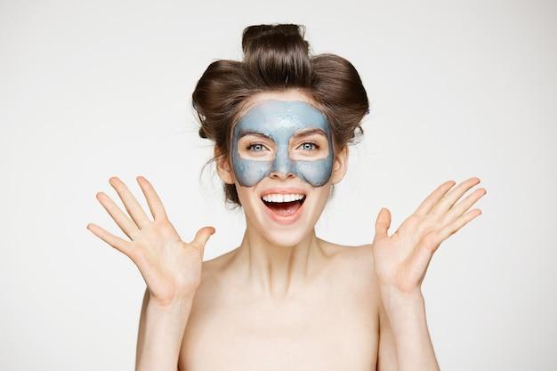 Schöne überraschte nackte frau in lockenwicklern und lächelnder gesichtsmaske. mund geöffnet. beauty health kosmetologie und hautpflege.