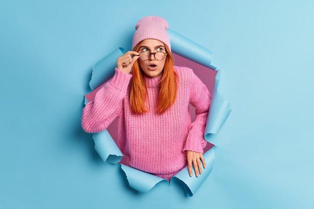 Schöne überraschte rothaarige junge frau hält den mund offen sieht etwas unglaubliches überrascht durch unerwartetes angebot trägt rosa hut und pullover bricht durch blaues papier