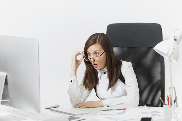 Schöne überraschte und empörte braunhaarige geschäftsfrau in anzug und brille, die am schreibtisch sitzt, am computer arbeitet, auf einen modernen monitor schaut, mit dokumenten im hellen büro,
