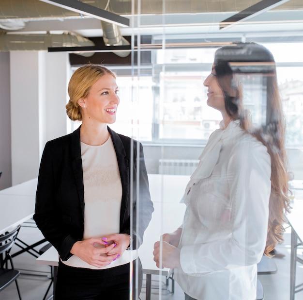 Schöne überzeugte geschäftsfrau zwei, die im büro steht
