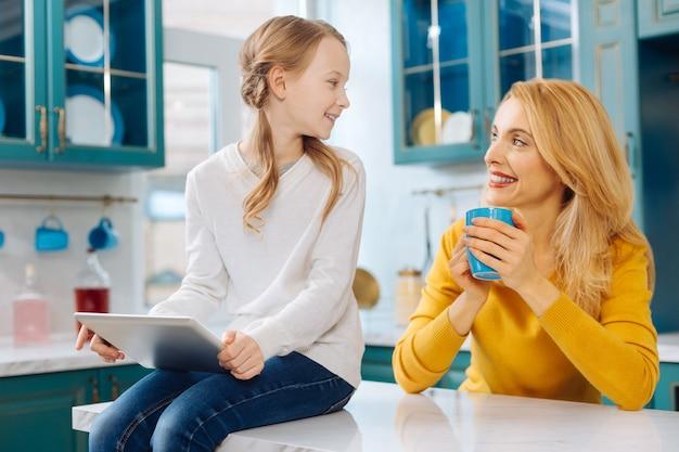 Schöne üppige blondhaarige schlanke mutter, die lächelt und eine tasse tee und ihre tochter mit einer tablette hält, während sie auf dem tisch sitzt