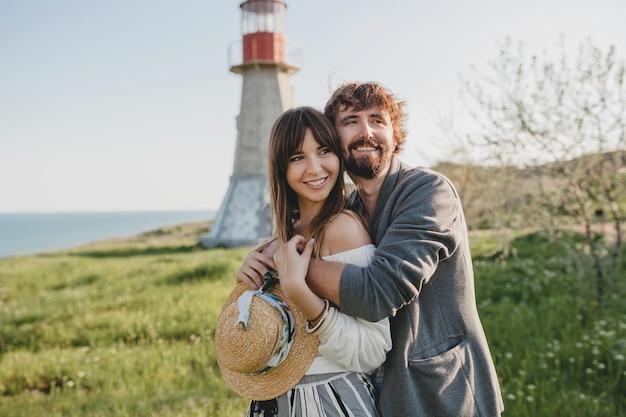 Schöne umarmung glückliches junges stilvolles hipster-paar in der liebe, die in der landschaft geht