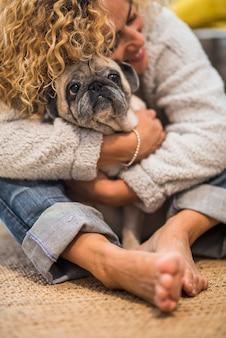 Schöne umarmung von mensch und tier für die haustiertherapie oder haushundeliebe und freundliche frau zu hause