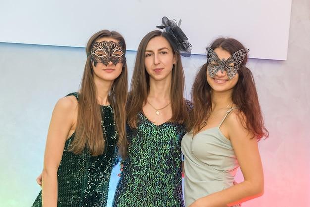 Schöne und attraktive frauen in maskeradenmasken und eleganten abendkleidern, die auf einer party posieren