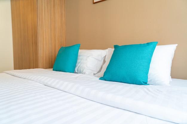 Schöne und bequeme kissendekoration auf dem bett im schlafzimmer