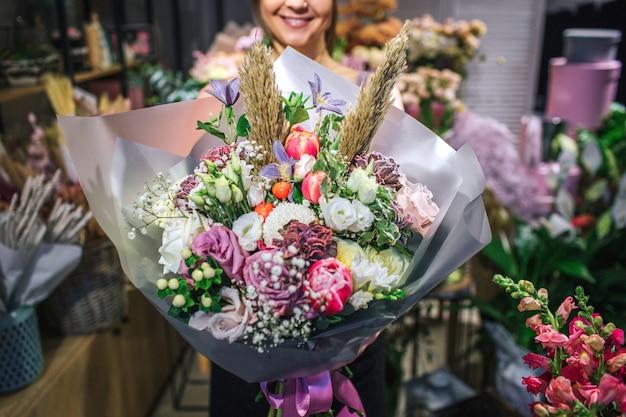 Schöne und bunte bouqette aus verschiedenen blumen. floristin halten es und lächeln. sie ist im blumenladen. schnittansicht. nahansicht.