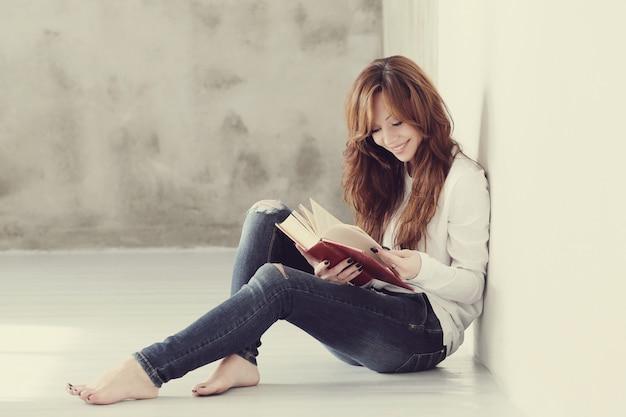 Schöne und charmante erwachsene frau, die ein buch liest