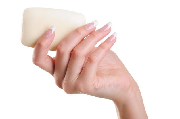 Schöne und elegante menschliche weibliche hand mit weißer seife